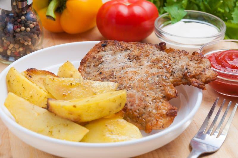 Côtelette de porc avec des tranches de pomme de terre dans un plat blanc sur un conseil en bois avec de la sauce Décoré des légum photo libre de droits