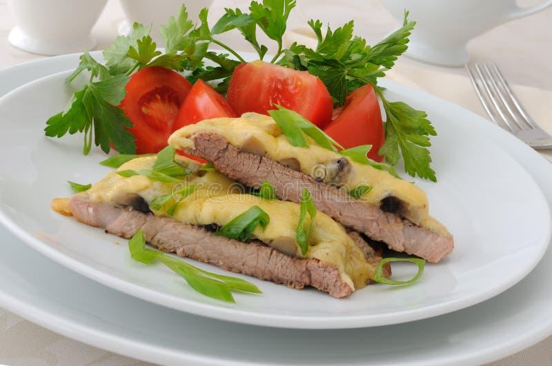 Côtelette de porc avec les champignons de couche et le fromage photos stock