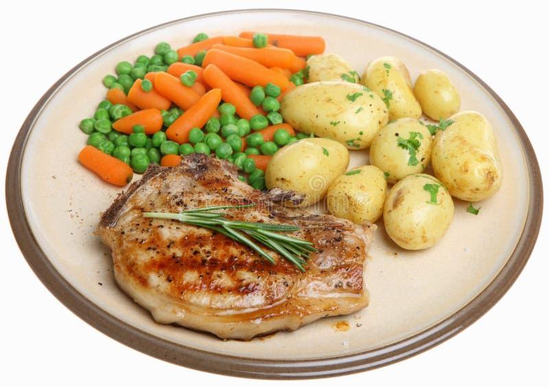 Côtelette de porc avec les pommes de terre de primeurs et les légumes image stock