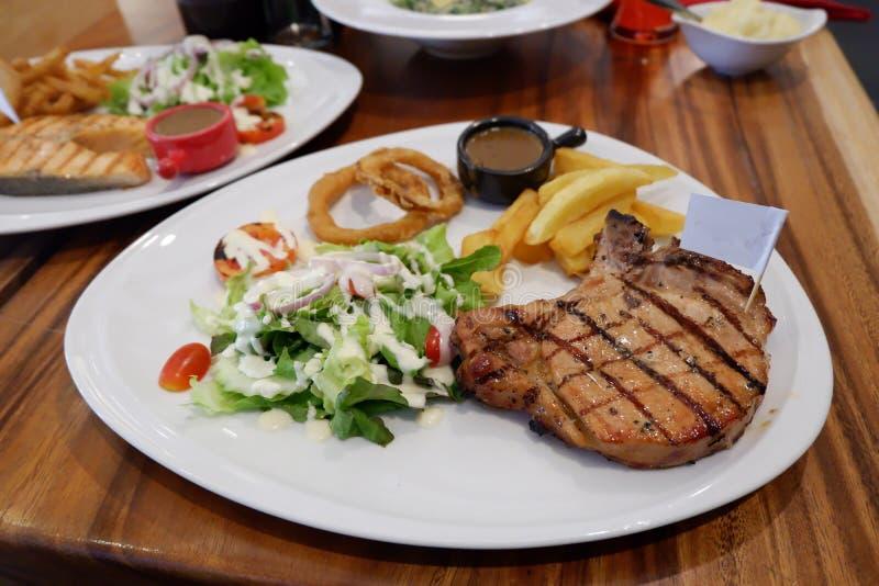 Côtelette de porc avec les pommes de terre de primeurs, les légumes et la sauce au jus image stock
