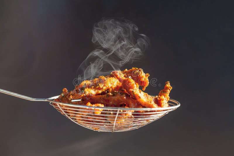 Côtelette de porc dans un panier qui a juste fait frire de la casserole dans la cuisine images stock