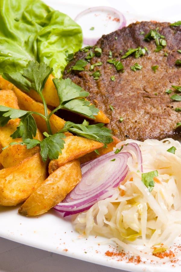 Côtelette de veau avec des lames de salade et de potatoe frit photographie stock libre de droits