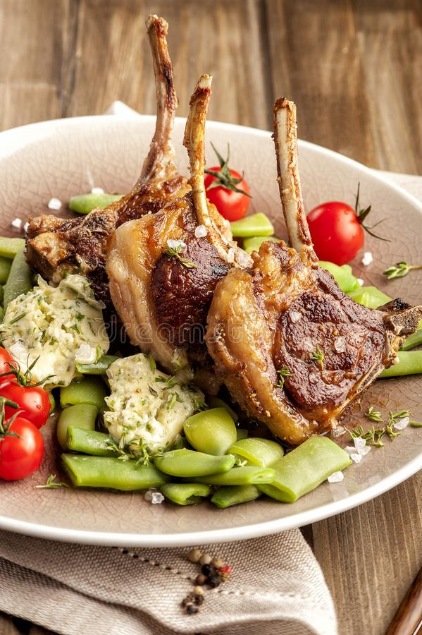 Côtelettes d'agneau grillées avec une garniture des haricots verts images stock