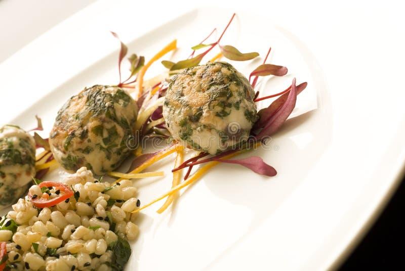 Côtelettes de poissons avec la mâche du plat blanc image libre de droits