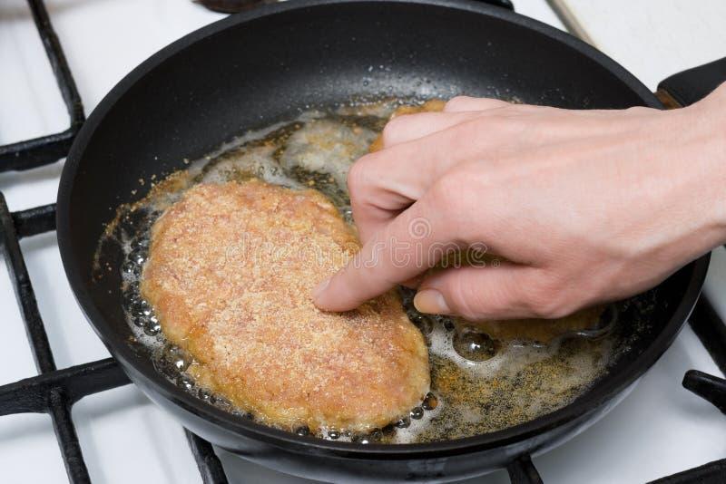 Côtelettes de poulet rôtissant sur la poêle image stock