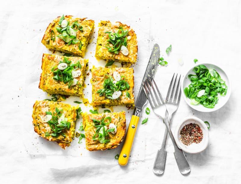 A cúrcuma, abobrinha, triturou a tortilha dos grãos-de-bico com ervas em um fundo claro, vista superior Aperitivos deliciosos imagens de stock