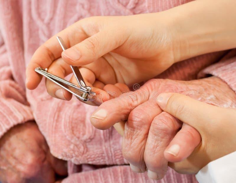 cążki pomaga gwoździa seniora kobieta zdjęcie royalty free