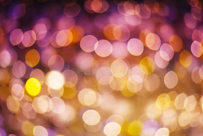 c的金和紫色抽象bokeh背景闪烁的星 免版税库存图片