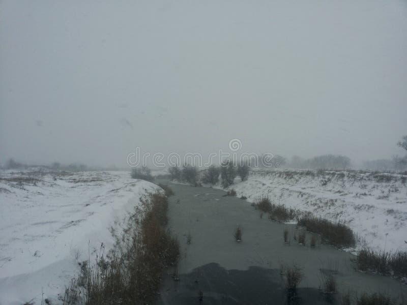 33c 1月横向俄国温度ural冬天 在冬天暴风雪中的一条小河 与一条河的明信片在冬天 低温 冻结河 免版税库存图片