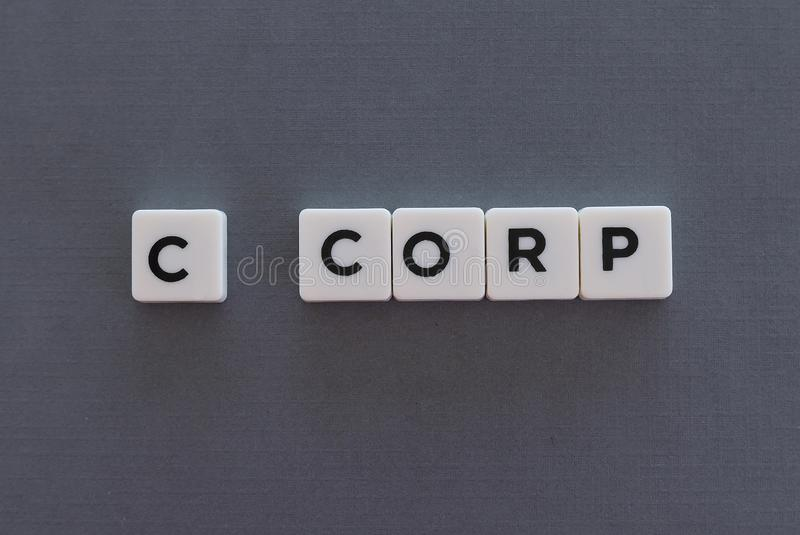 C corp word made of square letter word on grey background. Company business corporation corporate c-corp limited liability partnership llp financial concept royalty free stock image
