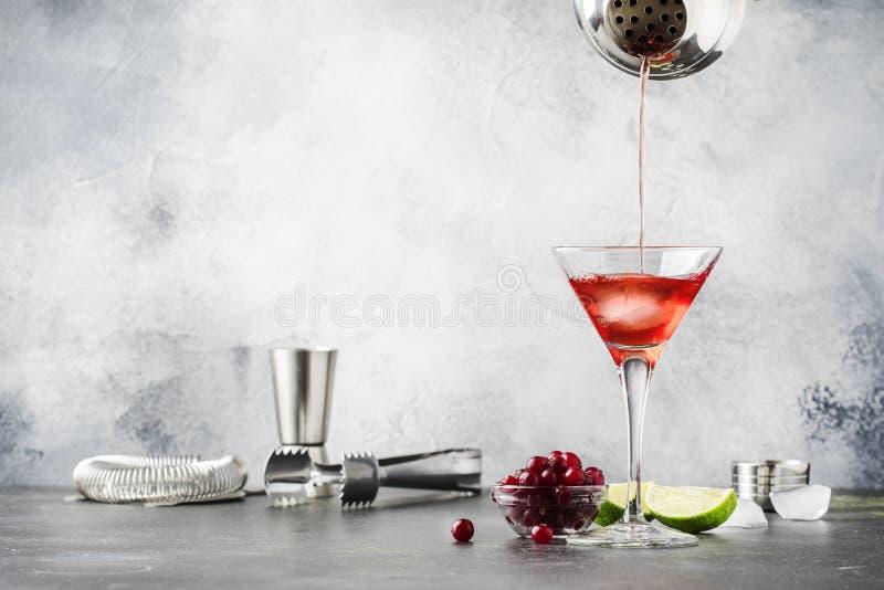 C?ctel alcoh?lico cl?sico de la preparaci?n cosmpolitan con la vodka, el licor, el jugo de ar?ndano, la cal, el hielo y el ?nimo  imagen de archivo libre de regalías