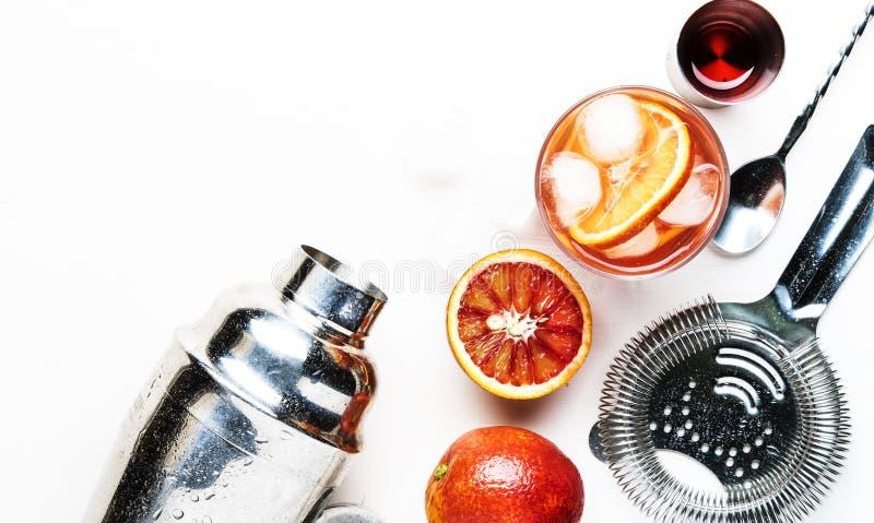 C?ctel alcoh?lico popular Negroni con ginebra seca, verm? rojo y cubos amargos, de la naranja y de hielo rojos Fondo blanco, herr foto de archivo
