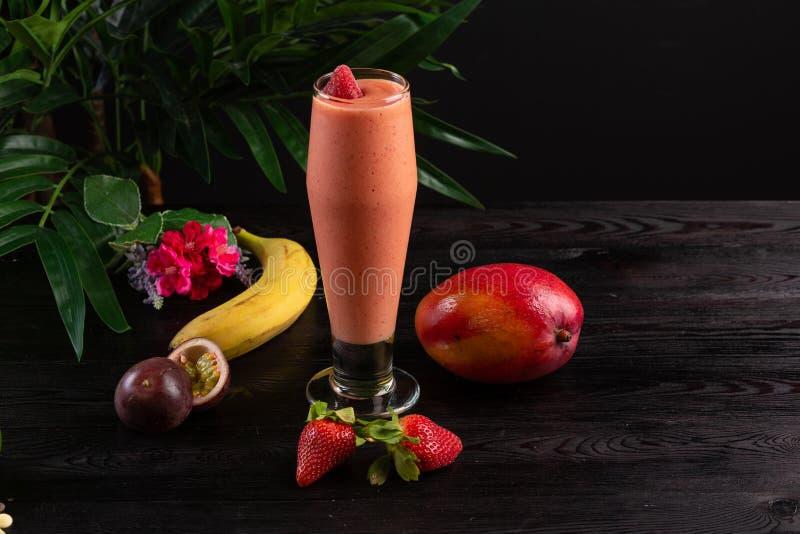 C?ctel con las frutas y las bayas en un vidrio alto en un fondo oscuro imagen de archivo
