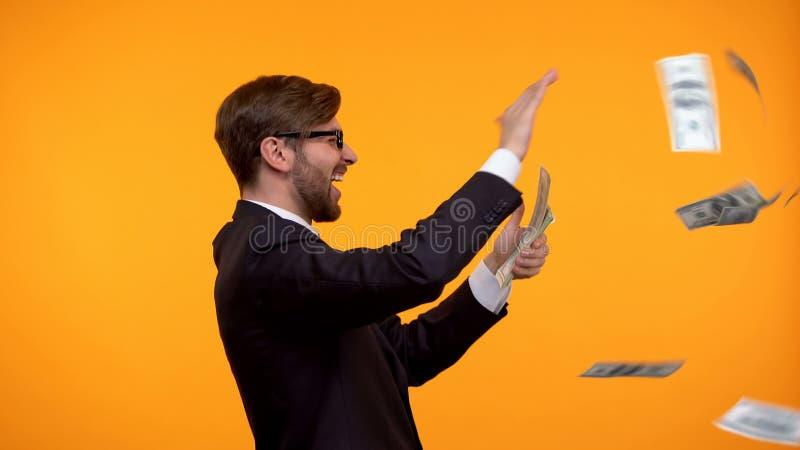 C?dulas de jogo do d?lar do homem de neg?cios positivo no ar, gastar dinheiro, sucesso foto de stock royalty free