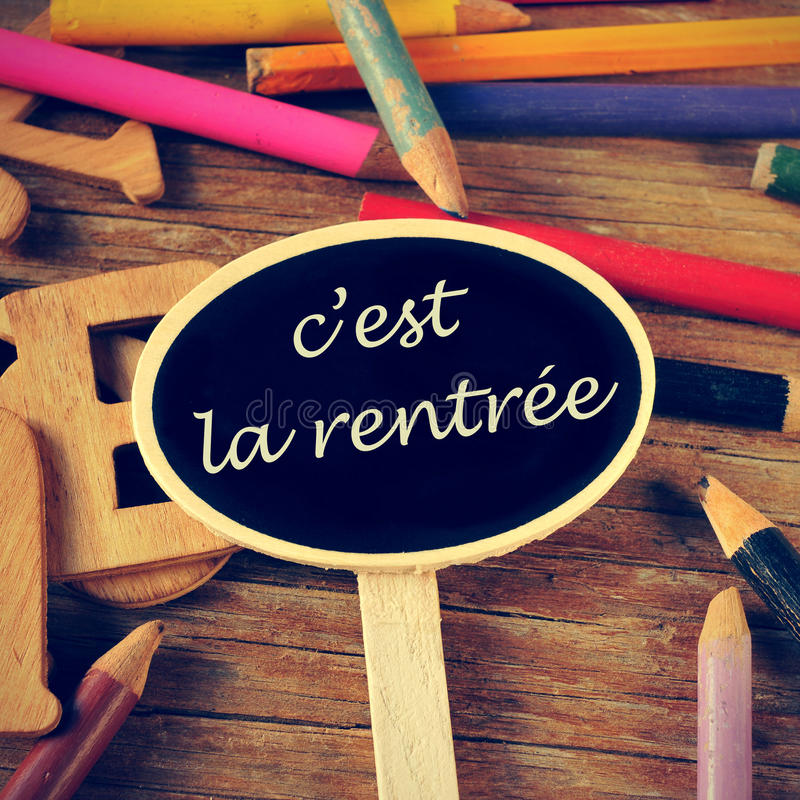 C'est la rentree, back to school written in french. The sentence c'est la rentree, back to school written in french in a blackboard label, on a wooden table and royalty free stock photography