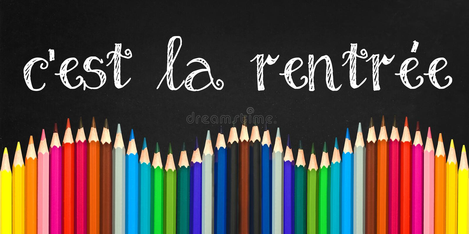 C`est la rentree meaning Back to school written on a black board background with a wave of colorful wooden pencils royalty free stock photography