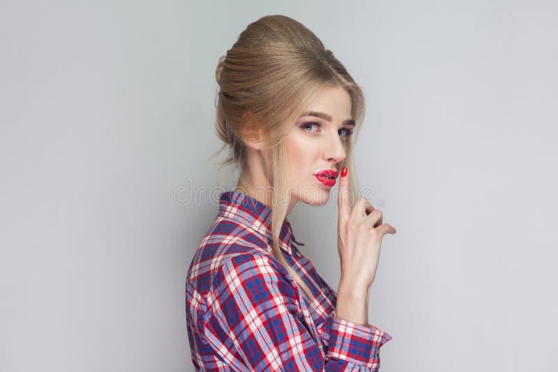C'est secret entre nous belle fille dans le shir à carreaux rose photo libre de droits