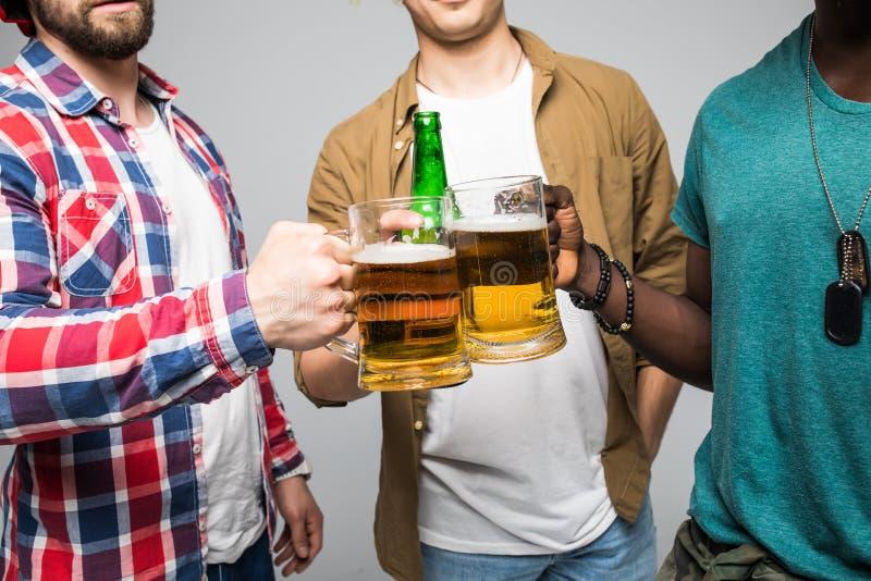 C'est un but Fermez-vous de trois jeunes hommes heureux faisant tinter avec des verres de bière d'isolement sur le gris photo stock