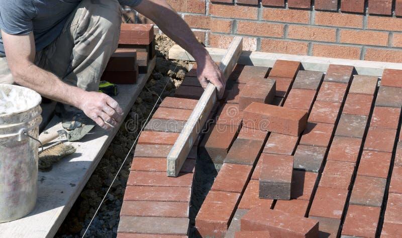 Maçon de brique étendant un trottoir images libres de droits