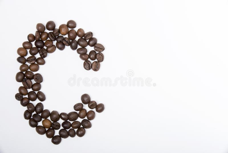 C - large letter of english alphabet. Made up of unmolished roasted coffee beans on a white background stock image