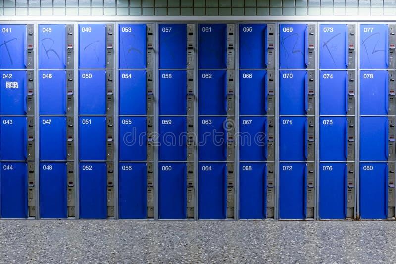 C?lulas en un almacenamiento azul del equipaje del color con llaves y una puerta abierta imágenes de archivo libres de regalías