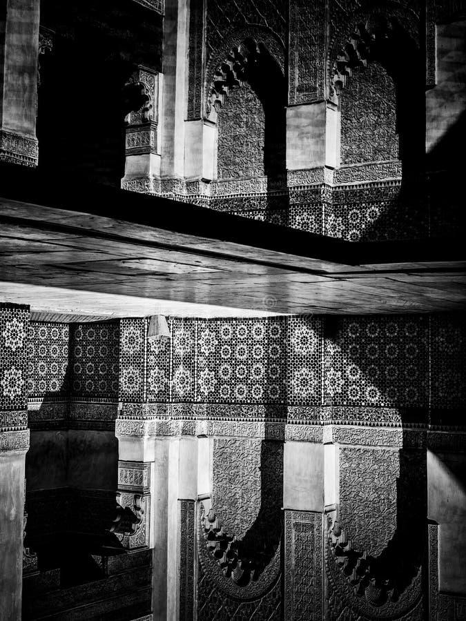 C4marraquexe, MARROCOS - 10 de fevereiro de 2012 - carvings do pátio molha reflexões em Ben Youssef Madrasa fotografia de stock