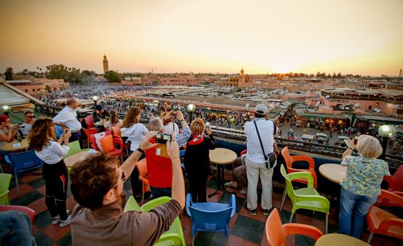 C4MARRAQUEXE, MARROCOS, EM JUNHO DE 2016: turistas que tomam imagens no sunse imagens de stock royalty free