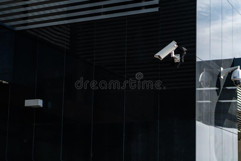 C?mera moderna do CCTV em uma parede Um fundo borrado da arquitetura da cidade da noite Conceito da fiscaliza??o e da monitora??o fotos de stock