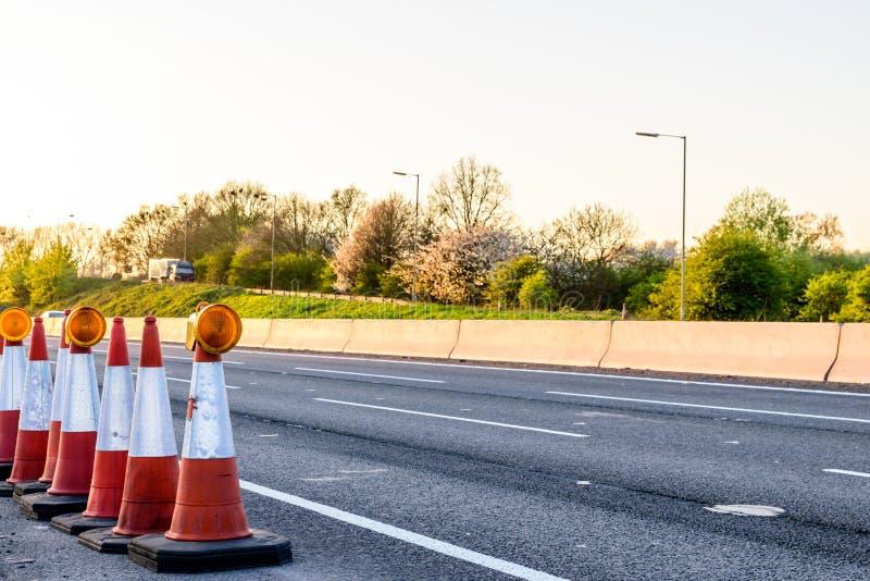 Cônes BRITANNIQUES de travaux routiers de relais d'autoroute de vue de soirée images stock