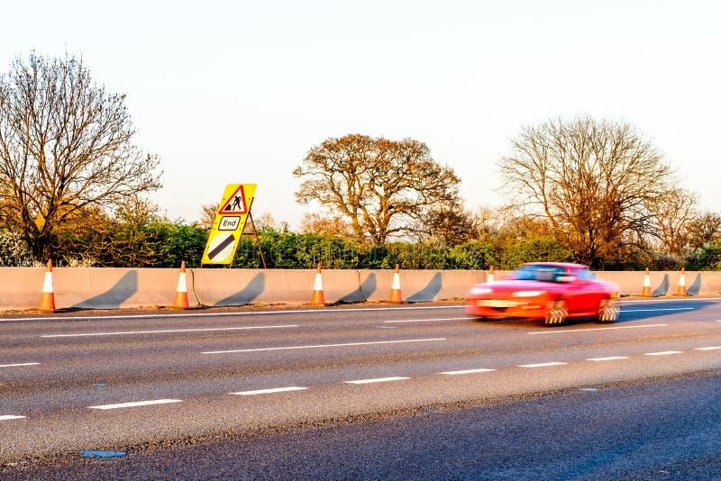 Cônes BRITANNIQUES de travaux routiers de relais d'autoroute de vue de soirée image stock