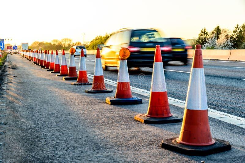 Cônes BRITANNIQUES de travaux routiers de relais d'autoroute de vue de soirée photo libre de droits