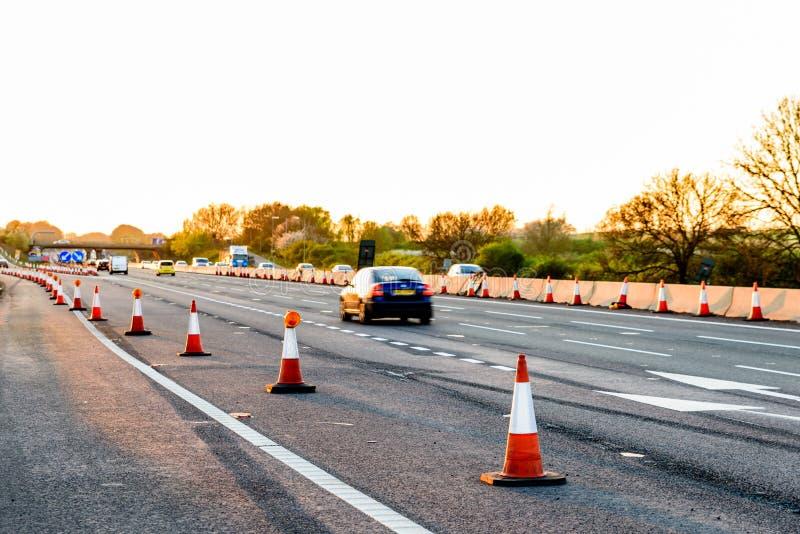 Cônes BRITANNIQUES de travaux routiers de relais d'autoroute de vue de soirée photo stock