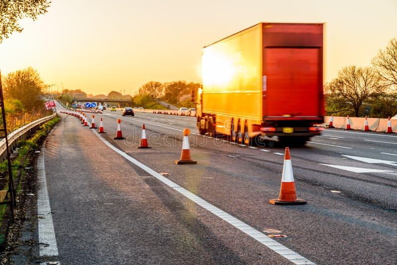 Cônes BRITANNIQUES de travaux routiers de relais d'autoroute de vue de soirée image libre de droits