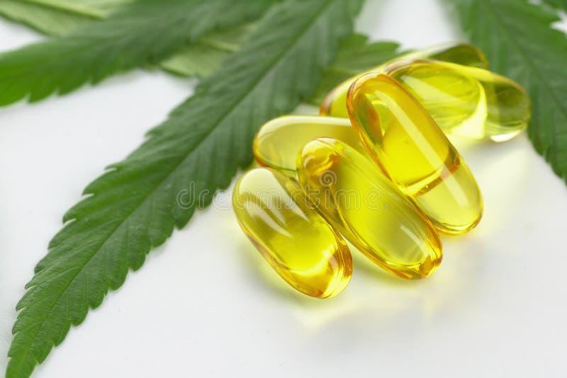 C?psulas do ?leo essencial do cannabis no fundo branco foto de stock