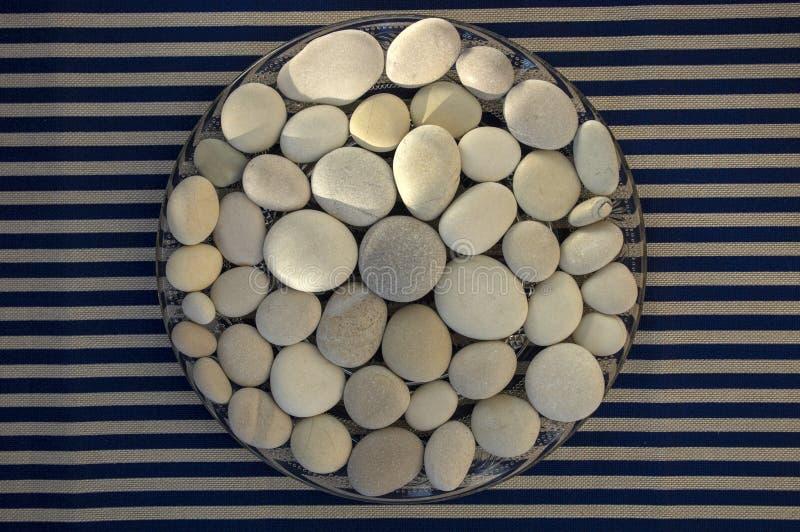 C?rculo composto das pedras brancas e cinzentas, fundo da mandala dos seixos no fundo listrado branco azul na luz do dia, conceit fotografia de stock