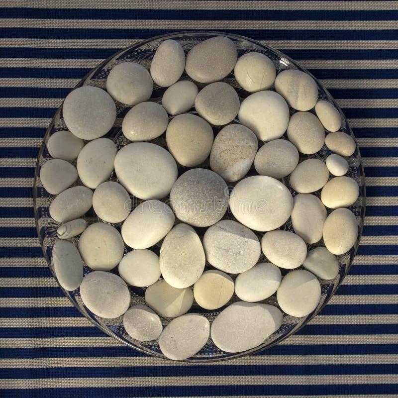 C?rculo composto das pedras brancas e cinzentas, fundo da mandala dos seixos no fundo listrado branco azul na luz do dia, conceit fotografia de stock royalty free