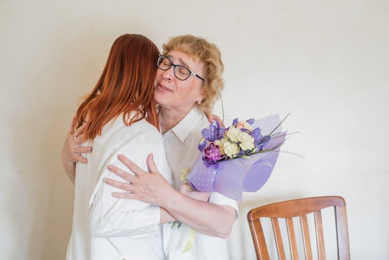 C?rka daje kwiaty doros?y matka ?zy szcz??cie C?rka daje kwiaty jej matka i ?ciska ona Wydawa? czas fotografia royalty free