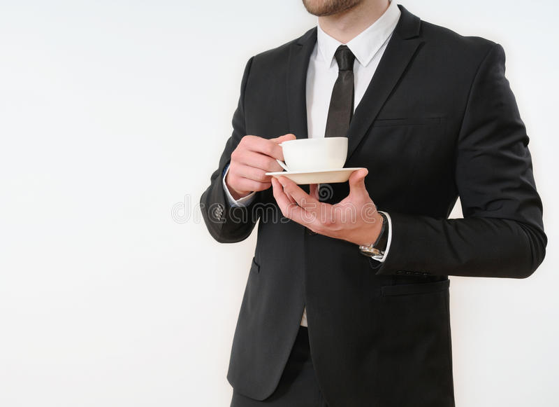 Côté de corps d'homme d'affaires dans le costume noir avec la tasse de café sur le blanc images stock