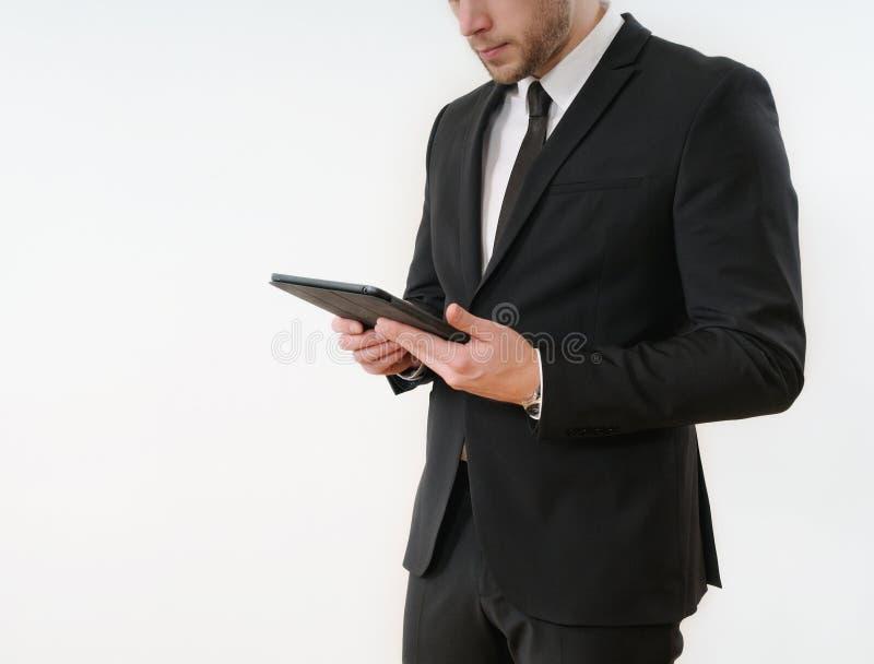 Côté de corps d'homme d'affaires dans le costume noir tenant son comprimé sur le blanc photos libres de droits