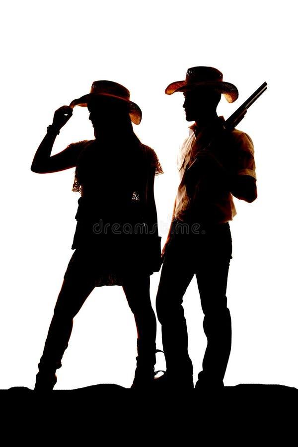 Côté de regard d'arme à feu de cow-girl de cowboy de silhouette photo libre de droits