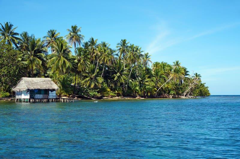 Côte tropicale avec la hutte rustique sur des échasses photographie stock