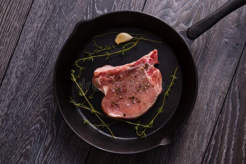 Côtelette de porc crue dans la casserole image libre de droits