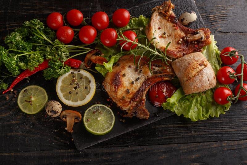 C?telette de porc frite d'un plat noir avec des ?pices, des herbes et des tomates image stock