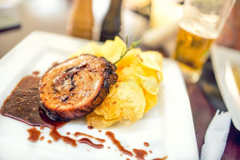 Côtelette de porc sur le gril avec des puces en tant que plat principal au restaurant local, plat de fantaisie de cuisine américa photographie stock libre de droits
