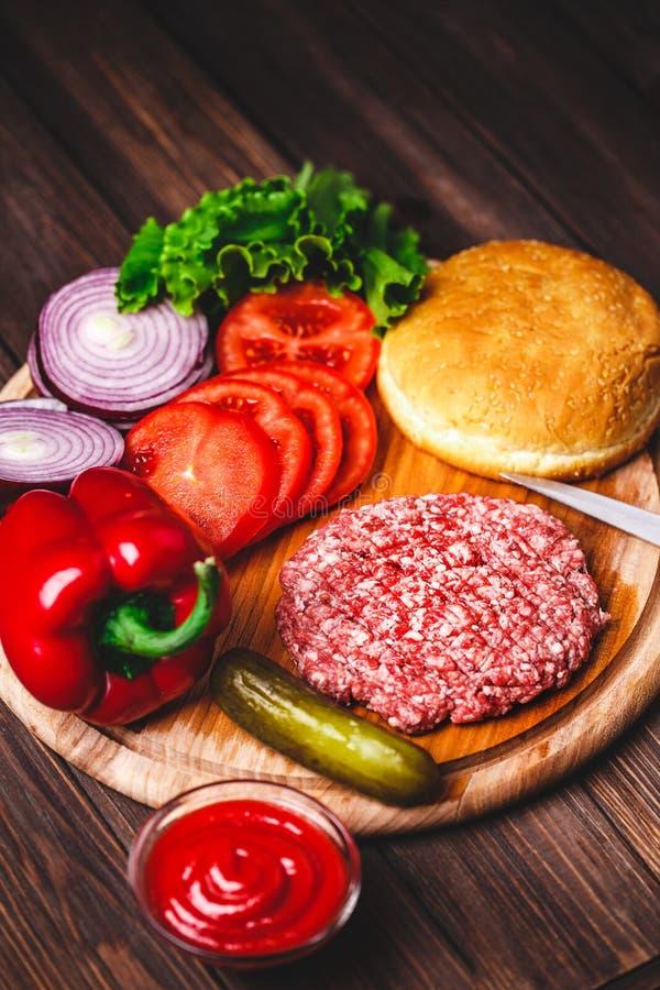 C?telettes crues de bifteck d'hamburger de viande de boeuf hach? avec l'assaisonnement, le fromage, les tomates, la salade et le  images libres de droits