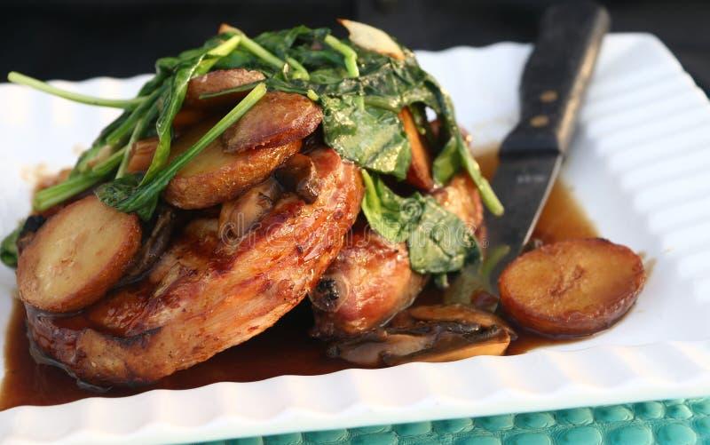 Côtelettes de porc avec des épinards et des pommes de terre de sauce au jus de champignon du plat blanc photographie stock libre de droits