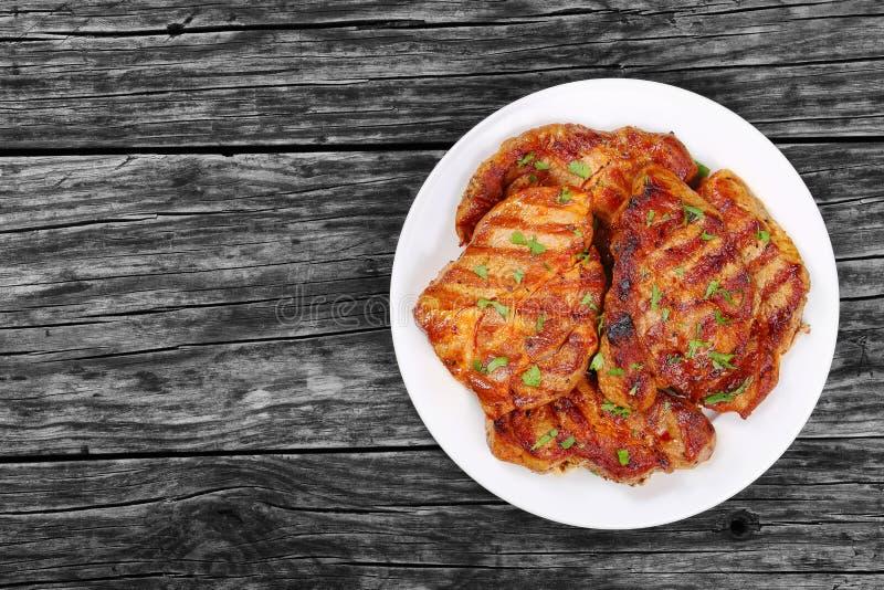 Côtelettes de porc juteuses du plat blanc image libre de droits