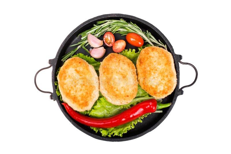 Côtelettes frites avec des légumes, des herbes et des épices dans une poêle photos stock