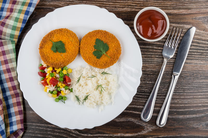 Côtelettes frites avec du riz, maïs, poivron doux, pois photographie stock
