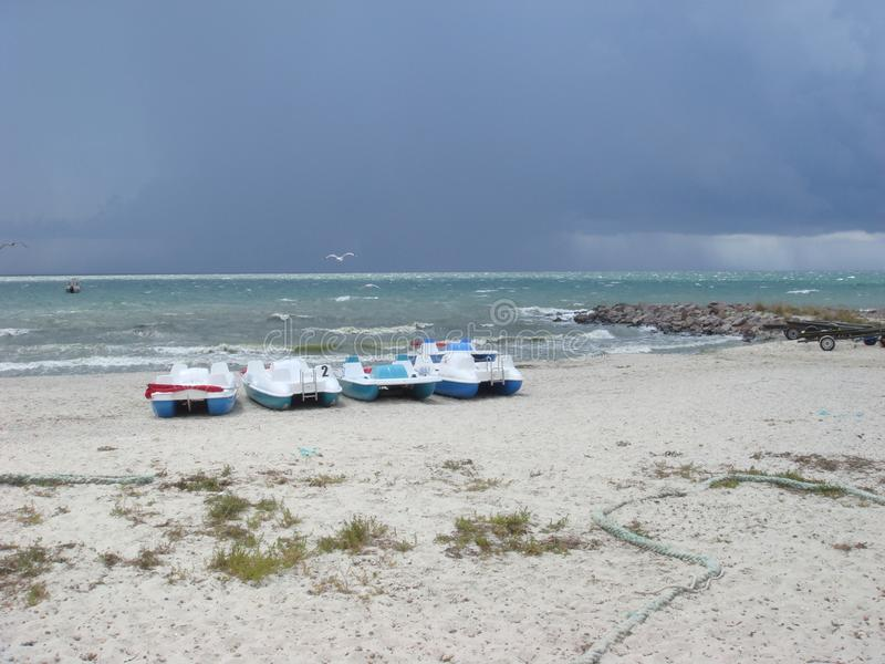 C?u nebuloso sobre o mar Nuvens de tempestade que formam sobre o mar claro Catamarãs em um Sandy Beach fotografia de stock